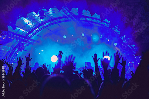 Abstract blur atmosphere: happy people enjoying outdoor music festival concert, raised up hands and clapping of pleasure, active night life concept, play of light and shadow on the stage