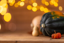 Pumpkins On Rustic Wooden Table With Yellow Lights Background. Autumn Harvest. Close-up View. Decoration Banner. Holiday Concept. Horizontal Format.