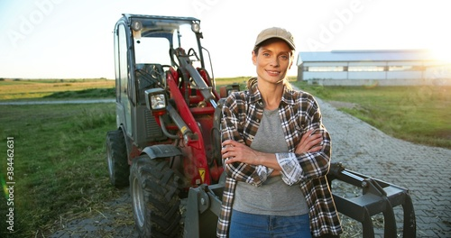 Portrait of beautiful Caucasian young woman in cap standing outdoors a big tractor machine and smiling cheerfully to camera Fototapeta
