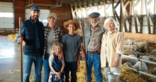 Portrait Of Happy Caucasian Family Of Three Generations Standing In Shed With Livestock And Smiling. Old Parents With Children And Grandchildren In Stable. Farmers At Farm. Indoor. Sheep On Background
