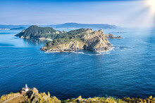 San Martiño Island Seen From The Top Of Montefaro In The Cies Islands, Galicia, With A Blue Atlantic Ocean And A Sky With The Sun Shining And In The Foreground With Yellow Vegetation And A Lighthouse