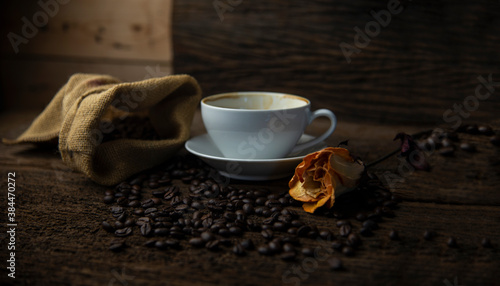 Obraz na plátně Coffee beans and coffee cup with coffee and coffee beans on table