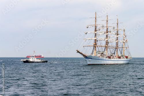 タグの先導で湾内を航行し、港に向かう帆船 © captainT