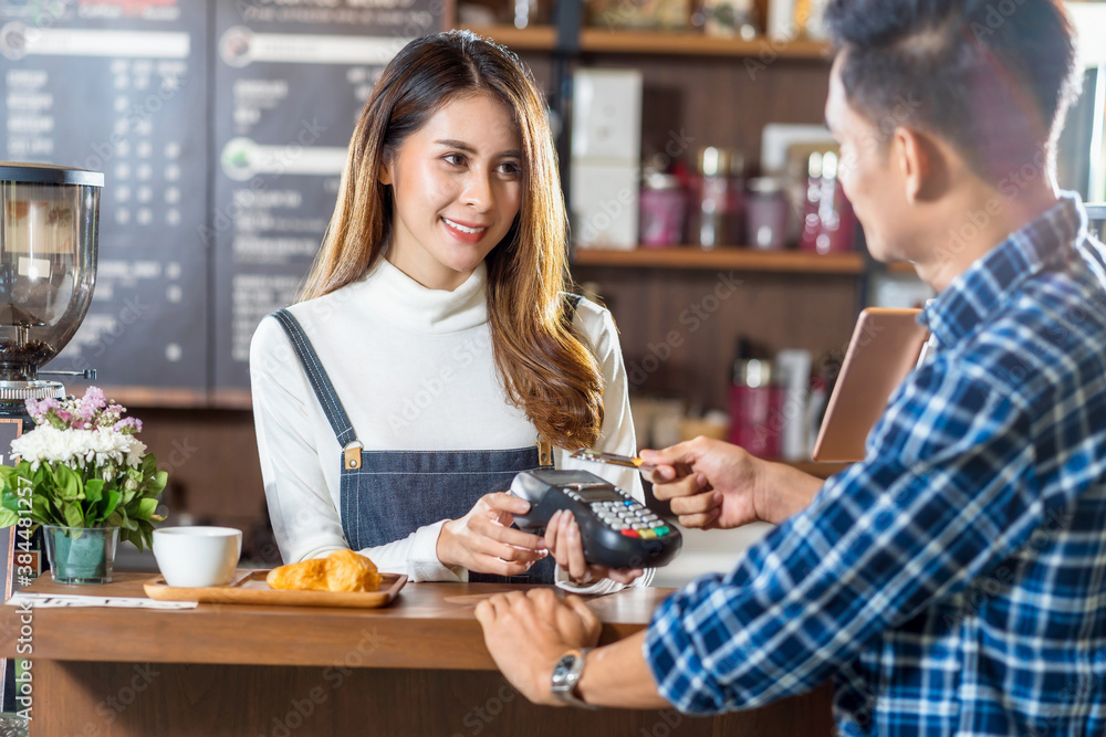 Fototapeta Asian customer man paying with credit card via contactless nfs technology to Asian Barista of Small business owner at the table in coffee shop, Small business owner and startup in coffee shop concept