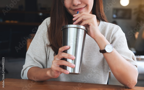 Obraz Closeup image of a beautiful asian woman drinking coffee in stainless steel cup - fototapety do salonu