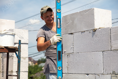 A worker builds the walls of a house from aerated concrete bricks Canvas Print