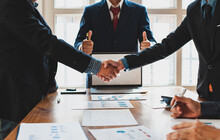 Business People Shake Hands While Negotiating A Business Deal. Concept Of Dispute Resolution And Mediation.