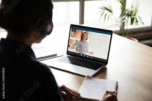 Back view of female student look at laptop screen watch webinar study online from home. Woman make notes have webcam digital lesson or training with teacher on computer. Distant education concept.