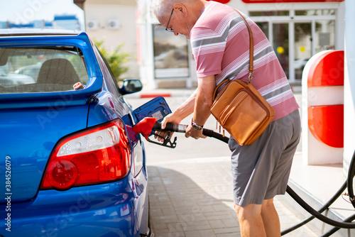 Obraz na plátně old senior man refill his car with gasoline on the fuel station, tourist traveli