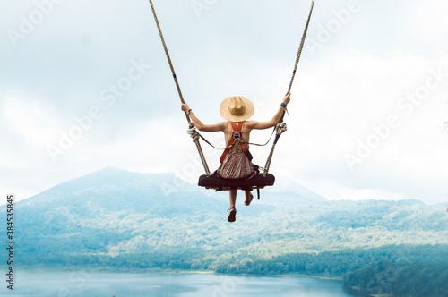 Obraz Beautiful girl enjoying freedom on swing in Bali, Indonesia - fototapety do salonu