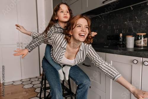 Photo Mom and daughter in similar shirts and jeans posing in kitchen and parody planes