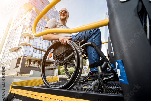 Tableau sur Toile A man in a wheelchair on a lift of a vehicle for people with disabilities