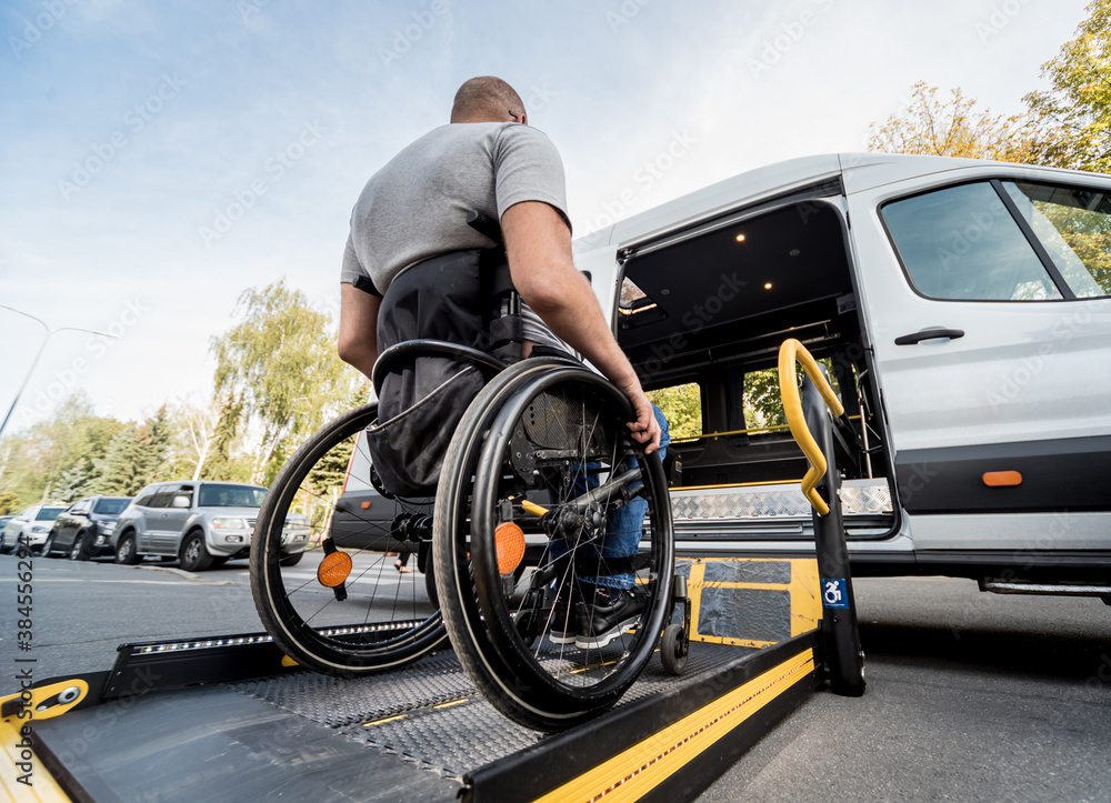 Fototapeta A man in a wheelchair moves to the lift of a specialized vehicle
