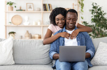 Loving African American Couple Using Laptop Together At Home