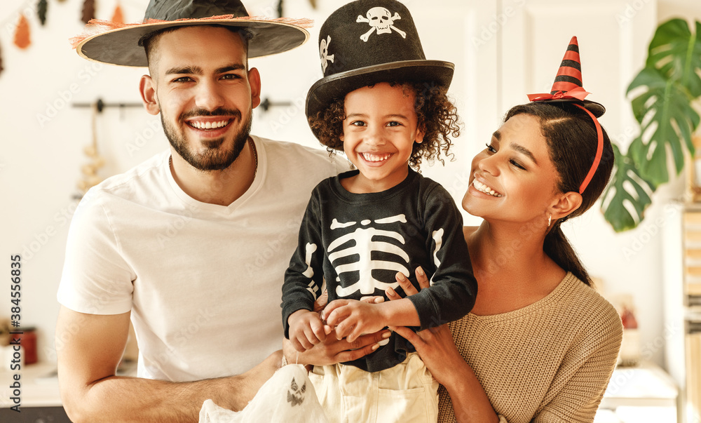 Fototapeta happy multiethnic family mom, dad and son have fun and celebrate Halloween at home.
