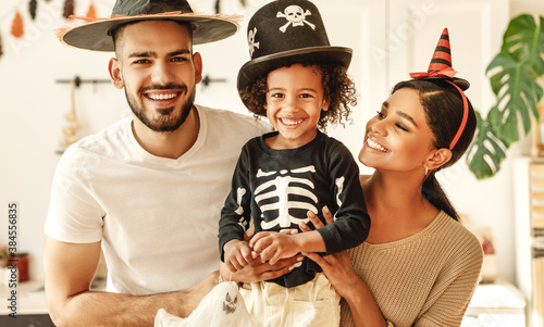 Fototapeta happy multiethnic family mom, dad and son have fun and celebrate Halloween at home. obraz