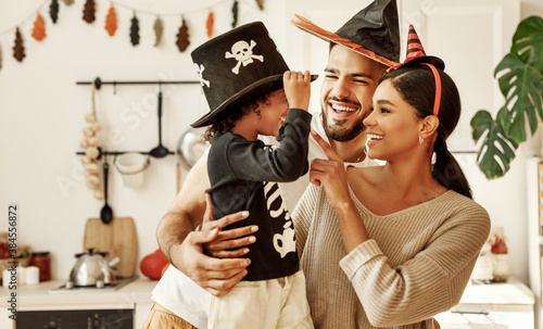 Obraz happy multiethnic family mom, dad and son have fun and celebrate Halloween at home. - fototapety do salonu