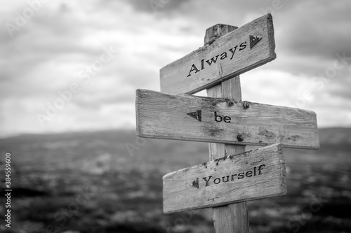 Fotografía always be yourself text quote on wooden signpost outdoors in black and white