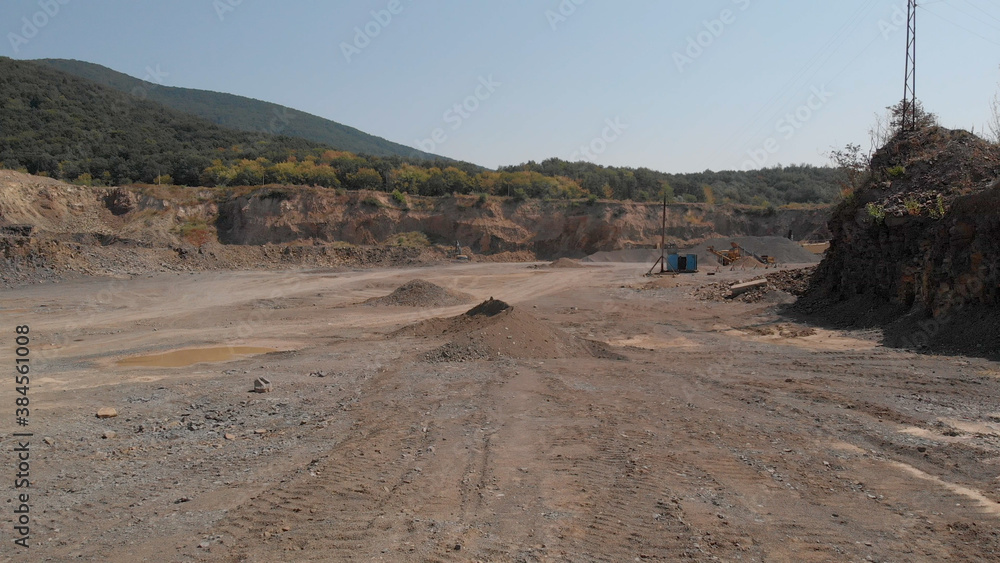 Fototapeta Sandy area of quarry. Object for construction and digging. Heaps of sand and puddles.