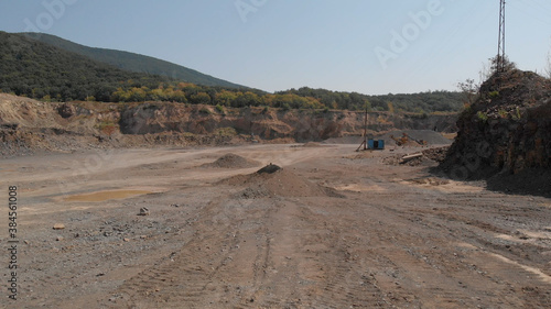 Obraz Sandy area of quarry. Object for construction and digging. Heaps of sand and puddles. - fototapety do salonu