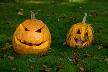 Two Pumpkins Jack Lantern On Green Grass For Halloween Party.
