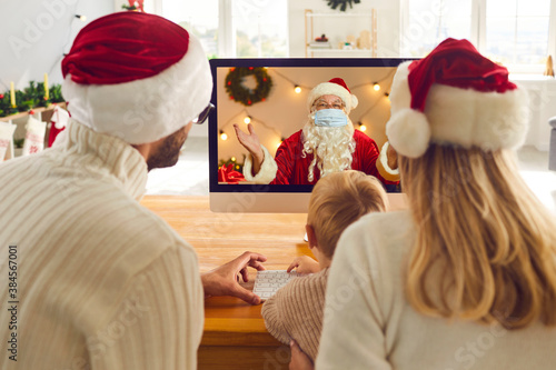 Fototapeta Parents and their little child having live video chat with Santa Claus during lo