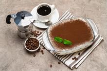 Traditional Italian Tiramisu Dessert In Glass Baking Dish, Cup Of Espresso And Mocha Coffee Maker On Concrete Background