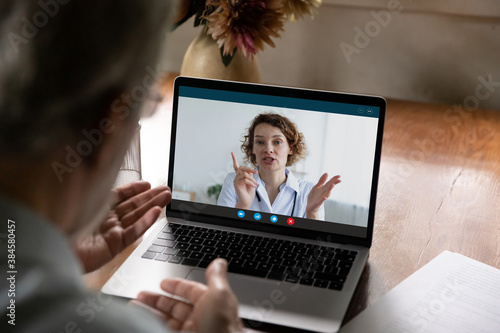 Rear view of mature man speak talk on video call with female doctor, have online consultation at home. Elderly male patient engaged in webcam digital conversation on computer with nurse or caregiver.