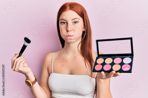 Cuadros en Lienzo Young red head girl holding makeup brush and blush palette puffing cheeks with funny face