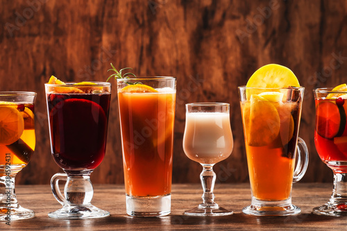Selection of autumn or winter alcoholic hot drinks and cocktails - mulled wine, glogg, grog, eggnog, warm ginger ale, hot buttered rum, punch, mulled apple cider on wood background, copy space