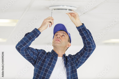 mature man installing ventilation grill in ceiling Wallpaper Mural