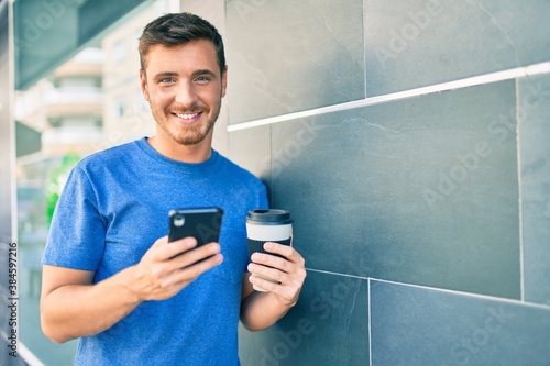 Obraz Young caucasian man using smartphone and drinking take away coffee at the city. - fototapety do salonu