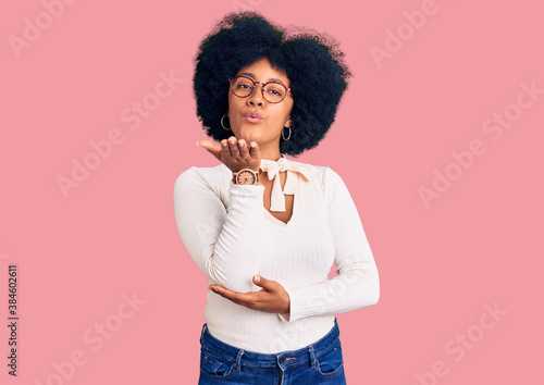 Fototapeta Young african american girl wearing casual clothes and glasses looking at the camera blowing a kiss with hand on air being lovely and sexy