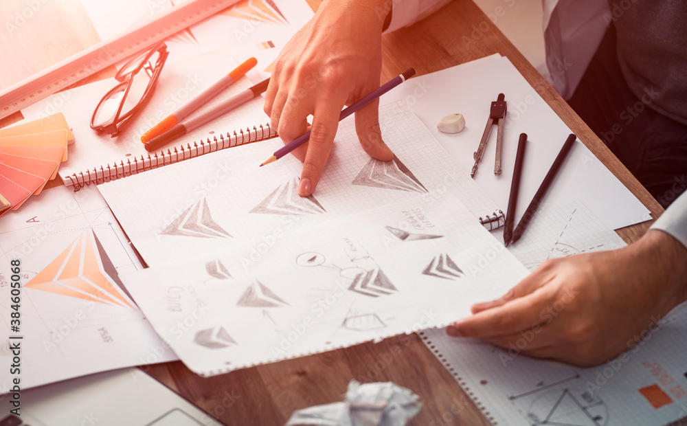 Fototapeta Graphic designer drawing sketches logo design.
