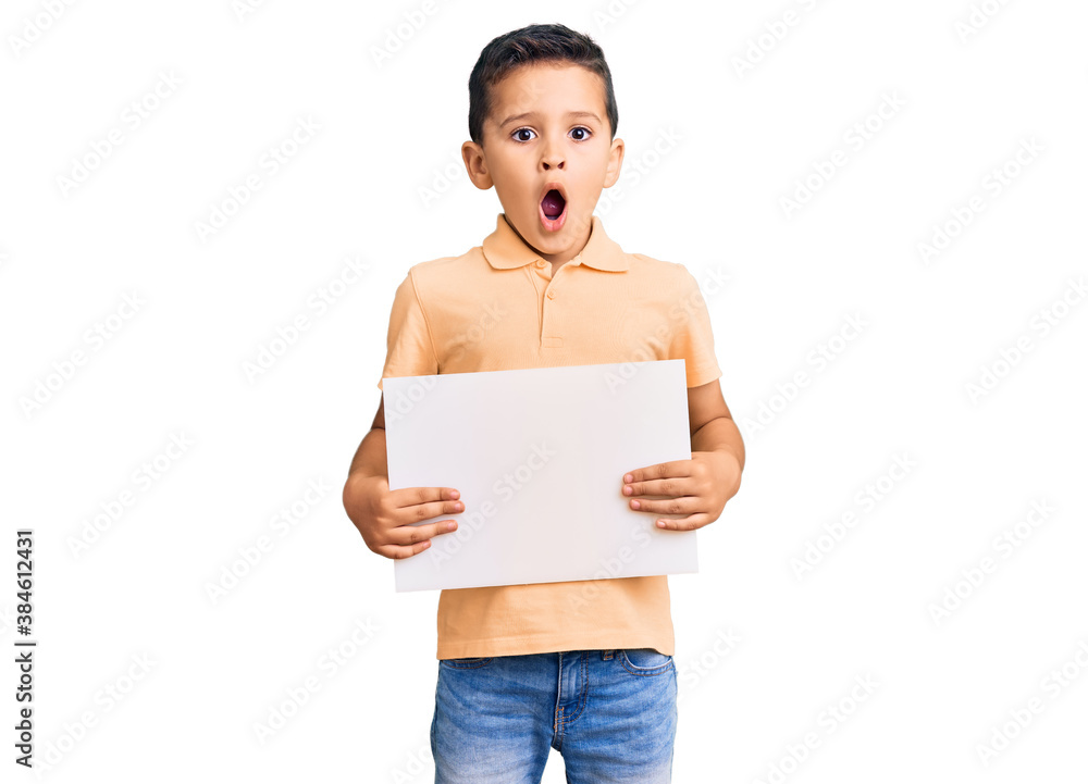 Fototapeta Little cute boy kid holding cardboard banner with blank space scared and amazed with open mouth for surprise, disbelief face