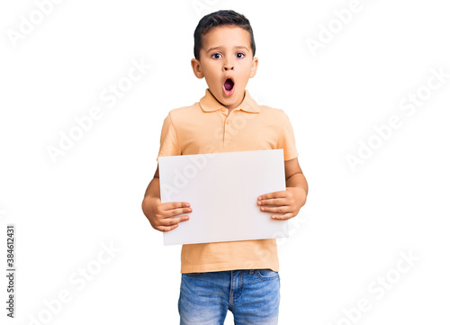 Fototapeta Little cute boy kid holding cardboard banner with blank space scared and amazed with open mouth for surprise, disbelief face obraz