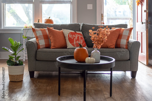 Home interior decorated for fall with orange accent pillows on the couch