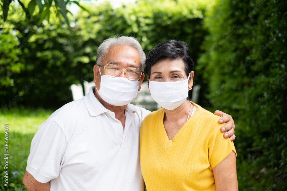 Fototapeta Senior old Asian couple, wearing face mask to protect coronavirus covid-19