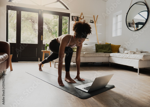 African American teen practising yoga flow watching video on laptop in modern lo Fototapet