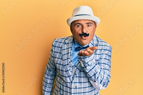 Fotografie, Obraz Mature middle east man with mustache wearing vintage and elegant fashion style looking at the camera blowing a kiss with hand on air being lovely and sexy