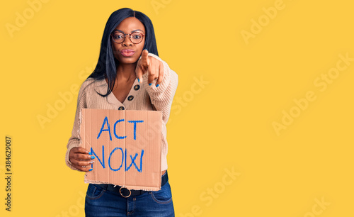 Fotografía Young african american woman holding act now banner pointing with finger to the