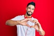 Leinwandbild Motiv Young man with beard listening to music using headphones smiling in love doing heart symbol shape with hands. romantic concept.