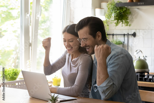 Fotografía Overjoyed young married couple making yes gesture, celebrating online lottery win or family success achievement, looking at computer screen, relaxing at modern kitchen table, good luck concept