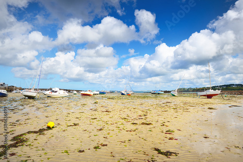 Fototapeta Yachts and boats during ocean low tide, close-up. Plouguerneau, Brittany, France. Clear sunny day, blue sky with lots of white clouds. Transportation, sport, recreation, leisure activity, tourism obraz