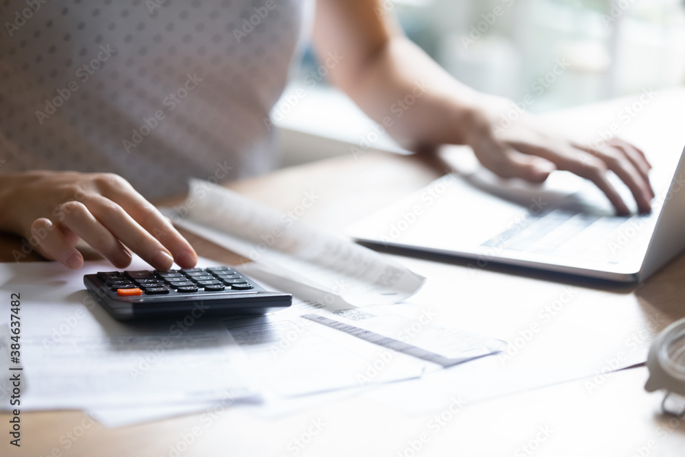 Fototapeta Close up young woman using calculator and computer applications, managing household expenditures, personal savings, medical insurance, education cost or taxes bills, making investments alone indoors.