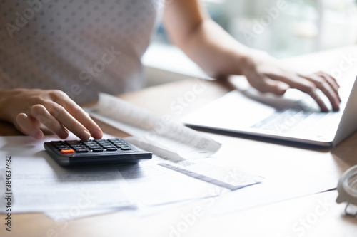 Close up young woman using calculator and computer applications, managing household expenditures, personal savings, medical insurance, education cost or taxes bills, making investments alone indoors. - 384637482
