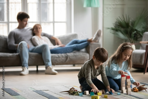 Obraz na plátně Small boy and girl children sit on warm floor in living room play with blocks or bricks together