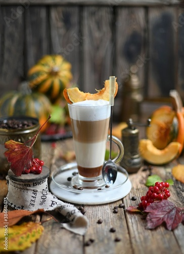 Pumpkin spice latte with whipped cream and cinnamon in glass on rustic wooden background. Selective focus.