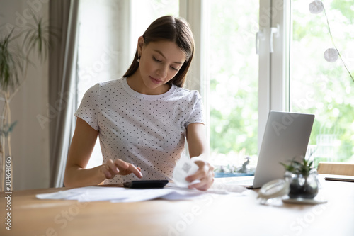 Fotomural Focused young pretty woman sitting at home office, calculating monthly expenses or checking bills at home