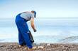 Leinwandbild Motiv Volunteer man standing on the beach with a full bag of collected trash
